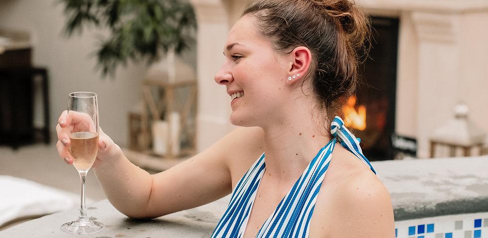 female enkoying champagne in hot tub