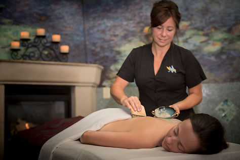 A massage therapist applying oil to a guest's back preparing for her treatment.