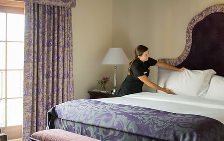 Housekeeping preparing a queen sized bed in one of our guest rooms.