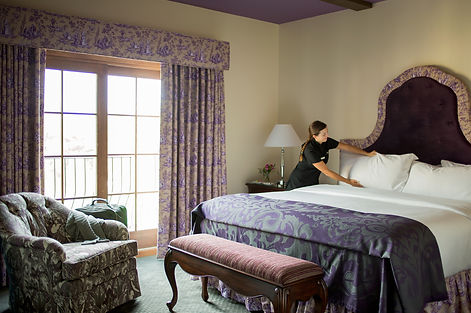 A housekeeper preparing a queen sized bed in one of our guest rooms.
