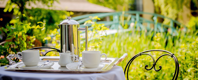 A pitch for coffee or tea with two cups outside a Monet inspired garden.