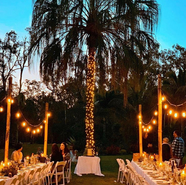 Garden cafe setup with lights strung along two long tables and lights around a palm tree