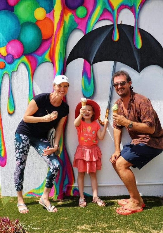 People enjoying ice cream, posing in front of the artfully painted wall at 1770 Gelato.