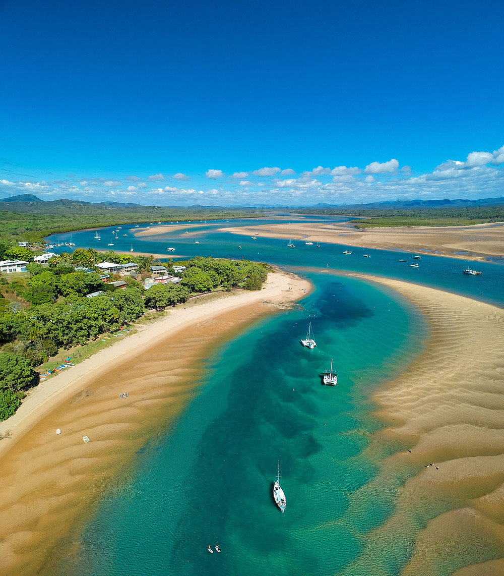 An aerial image of the creek in 1770 at low tide. Clear, turquoise, green and blue water intercepted by various sandbanks and sailing vessels moored.. Hills in the background