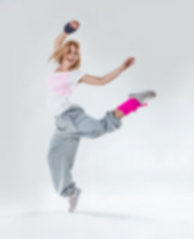 Young beautiful slim girl dancing on a w