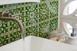 אריחים מעוטרים בירוק על קיר מקלחת