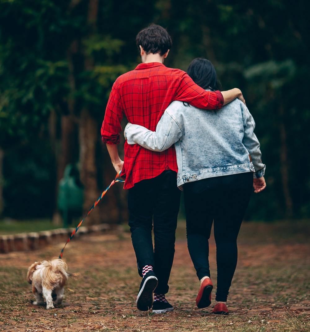 Couple walking with their dog on a trail