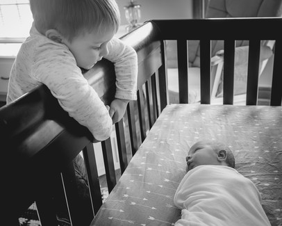 Newborn Lifesyle session one week old baby in crib with sibling looking at him
