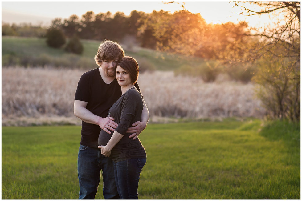 Husband and wife standing in a field with their hands on her pregnant belly during golden hour.