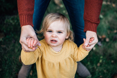 toddler girl holding on to moms hand looking up at the camera with her baby teeth showing