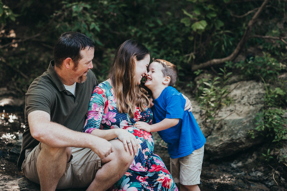 Family photo in a creek mom dad and son maternity pregnant greenery