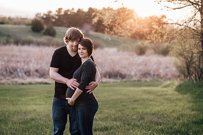 Man and woman husband wife pregnant taking maternity photos in a field during golden hour sunset wearing black