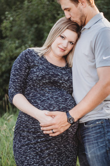 Outdoor maternity session with dad kissing the top of moms head hands on belly