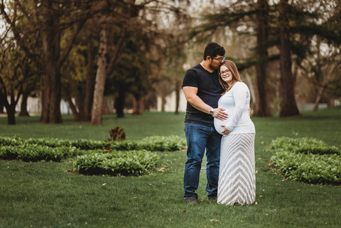 Outdoor maternity session in St Cloud MN dad kissing moms head hands on belly