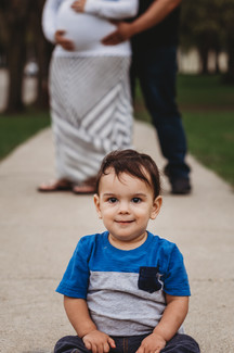 Outdoor maternity session toddler brother sits on sidewalk with mom and dad in background