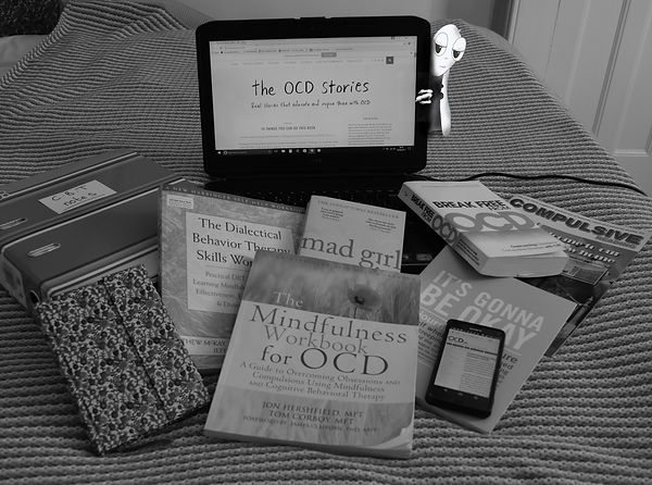A picture of Olivia amongst my OCD books, CBT work and helpfu websites