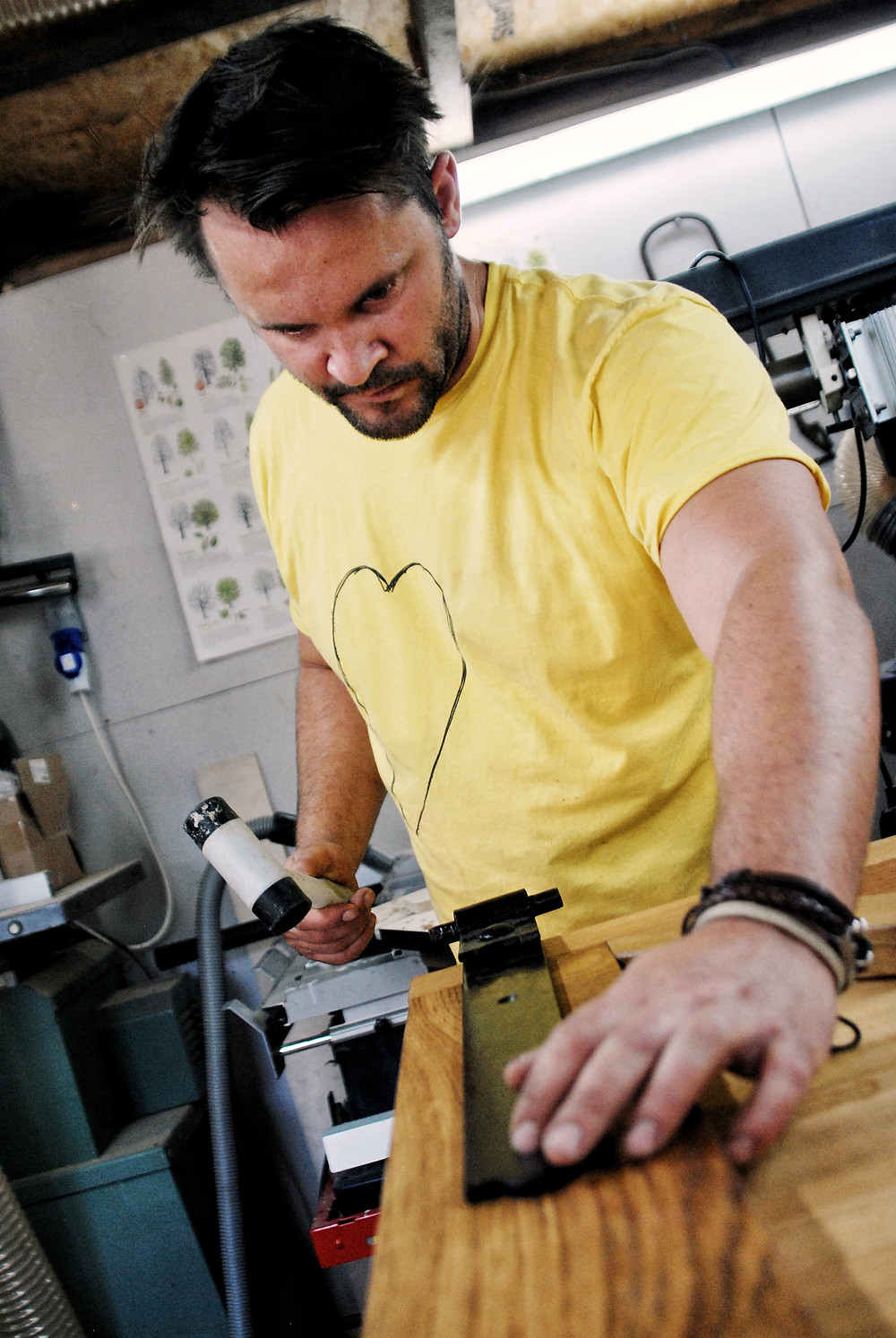 Man in yellow t-shirt working with wood in a workshop