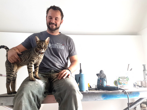 Man sitting on a workbench stroking a cat standing on his knee