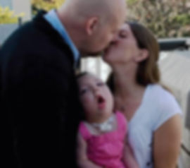 A couple share a loving kiss with their daughter between them.