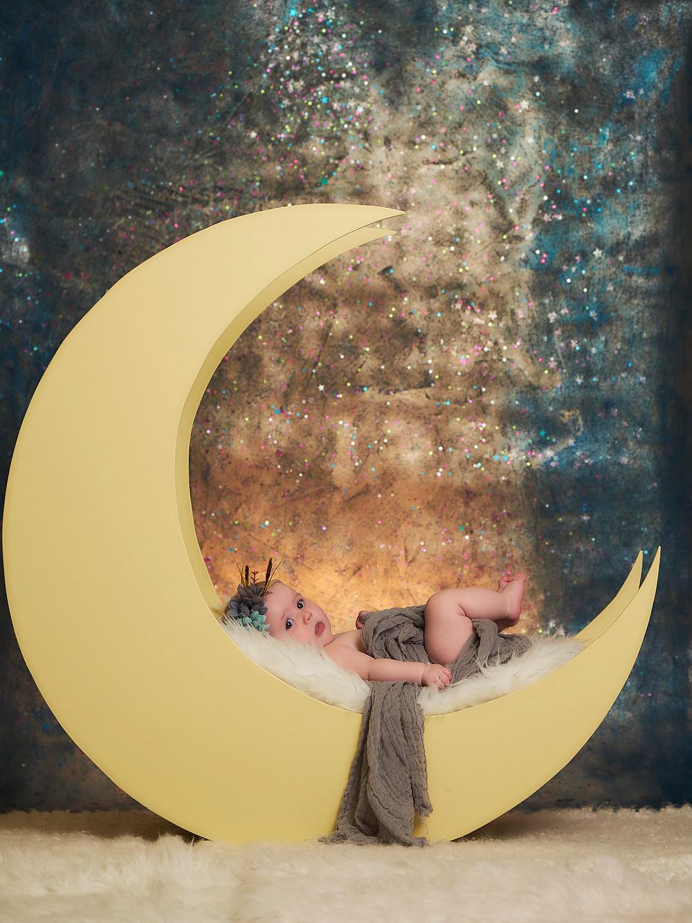 newborn on crescent moon at Happy Kids Photo Studio