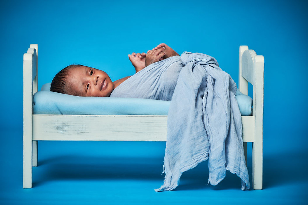newborn baby in a baby bed on blue backdrop