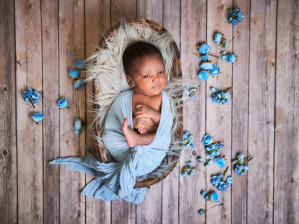baby boy in a oval crate on a wooden backdrop with blue flowers