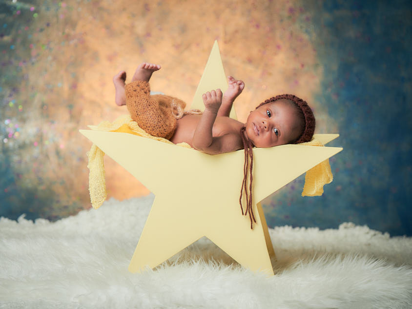 newborn baby on a star with unique backdrop