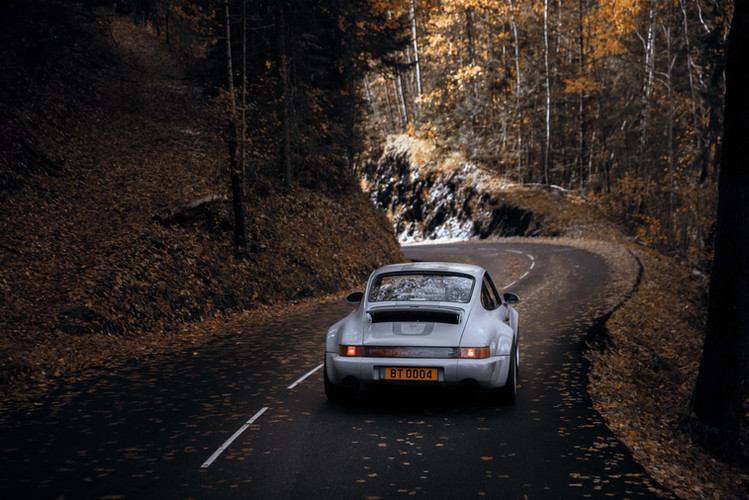 Restomod car BT04 view from the back, driving in the Alps (France)