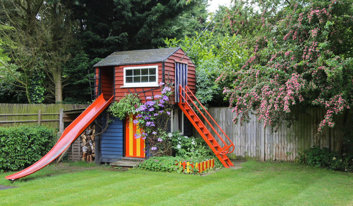 Well maintained garden with tree house, slide and swing for your children
