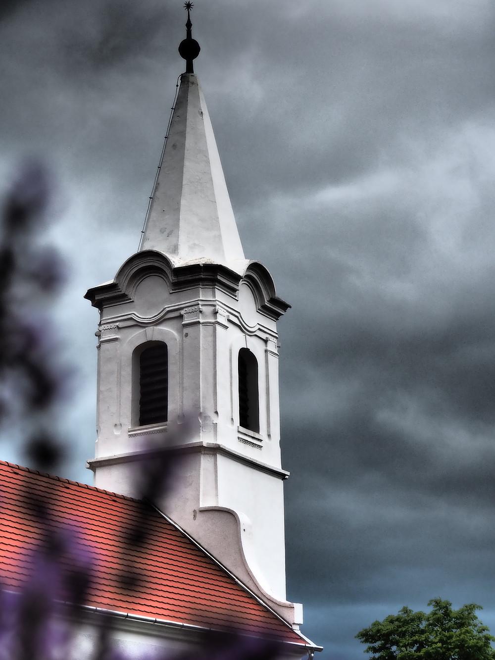 Balatonudvari egyik fehér templomtornya, egy egy nyári vihar sötét felhőivel a háttérben • Saját fotó