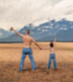 un bambino e suo padre insieme in montagna innalzano al cielo ciò che hanno raccolto insieme
