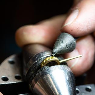 Der Fasser setzt weiße Diamanten/vs in die Öse. Handarbeit von höchster Präzision und Konzentration.