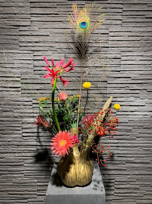 Mooie vaas in mat goud gevuld met seizoensbloemen