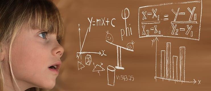Girl working math problem on chalkboard