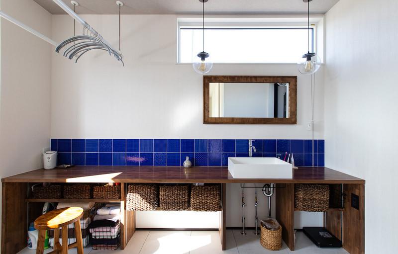 幅広の使いやすいカウンターと美しいブルーのタイルが目を引く造作の洗面台。洗濯物を干したりアイロンがけをしたりするなど家事ラクな家を実現