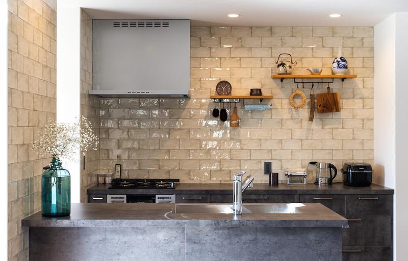 お洒落なタイルやセラミック製のワークトップ、背面の「魅せる」収納棚などがスッキリとしながら可愛らしい雰囲気を醸し出すキッチン