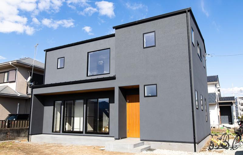 黒い外壁や1・2階の大きな窓が目を引くモダンな外観