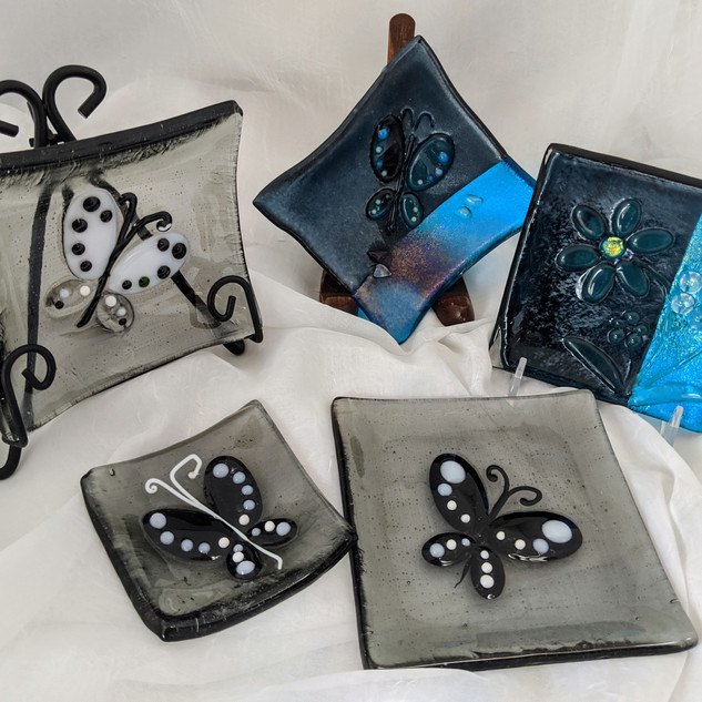 frontleft-MSA 0397Trinket dish-Black and white butterfly on grey fused glass$18, rearleftMSA 0400Dish Square-Black and white dimensional butterfly on grey fused glass$26, rearMiddle-MSA 0401Square bowl-Clear dimensional butterflies on turquoise 2-toned iridized fused glass $26 , rearRight-SOLD
