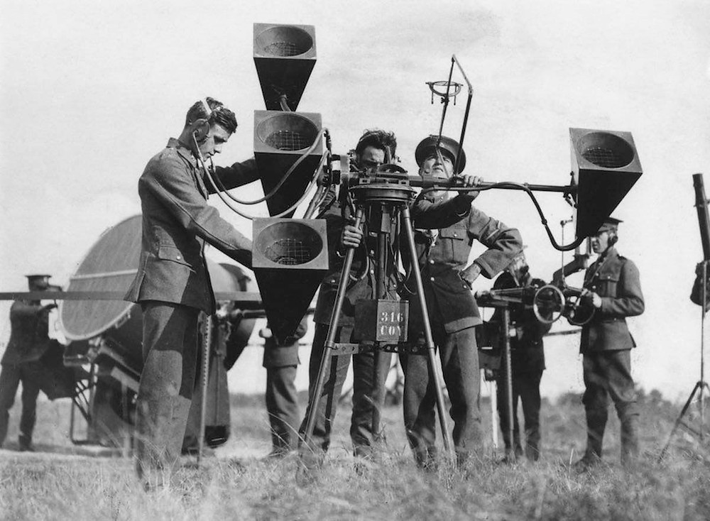 A four-horn acoustic locator again, in England, 1930s. There are three operators, two with stethoscopes linked to pairs of horns for stereo listening.