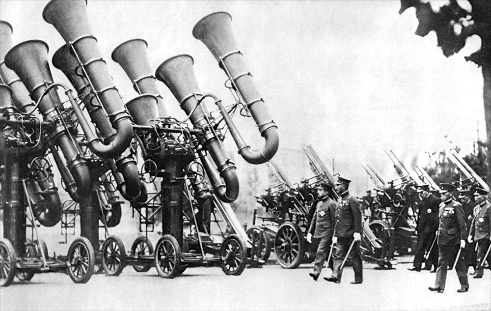 "Three Japanese acoustic locators, colloquially known as ""war tubas"", mounted on four-wheel carriages, being inspected by Emperor Hirohito."