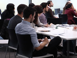 Photograph of a group of people listening to a presentation during a Postdocs to Innovators (p2i) training workshop