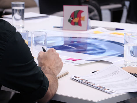 Photograph of a man writing notes on a business plan canvas