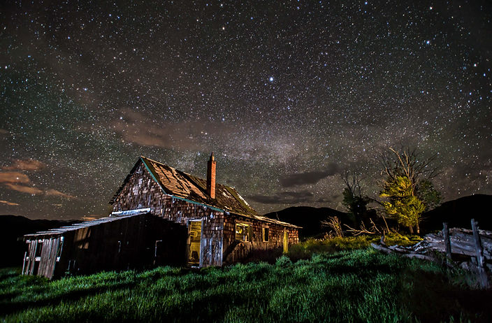 An old cabin homestead under a night sky and brilliant milky way stars in western Colorado.jpg