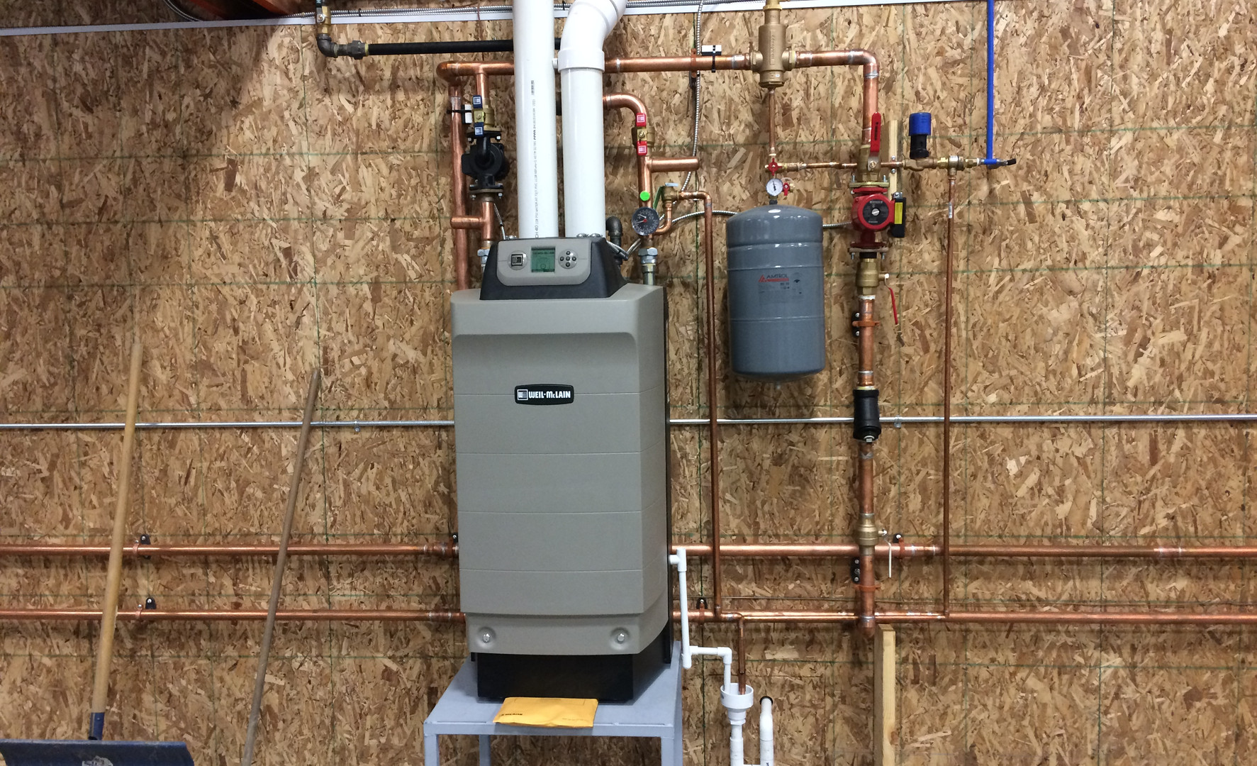 High-efficiency condensing boiler radiant floor heating system installation for a garage
