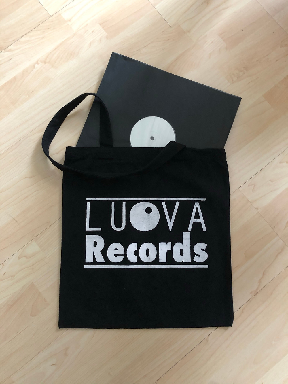Vinyl record sleeve showing a white label, peeking out from a Luova Records tote bag