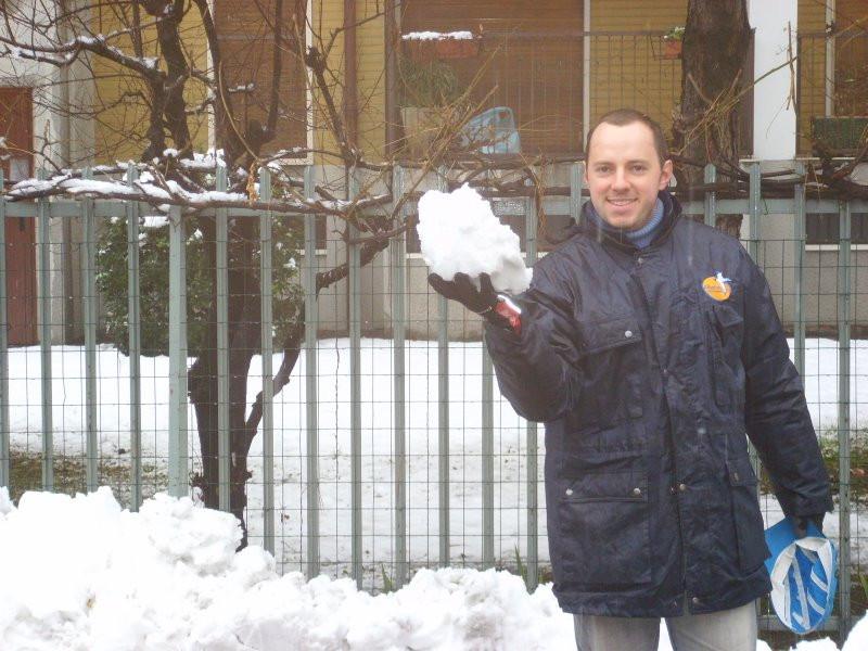 homem segurando neve em frente a casa