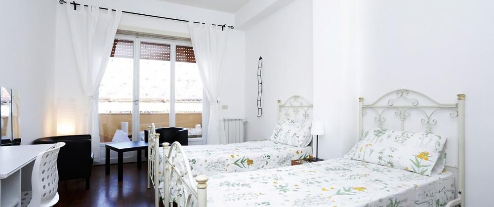 quarto com duas camas, janela ao fundo