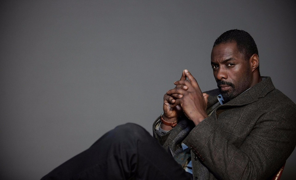 Idris Elba sitting and staring