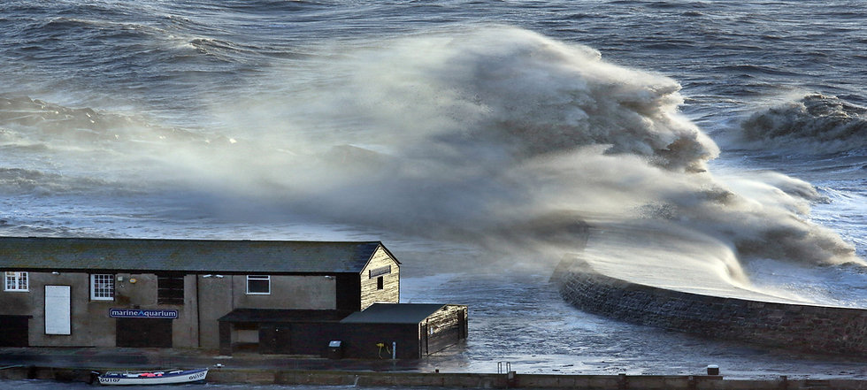 Stormy seas crash over Lyme Regis Harbour.