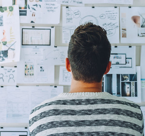 Designer looking at wall of projects